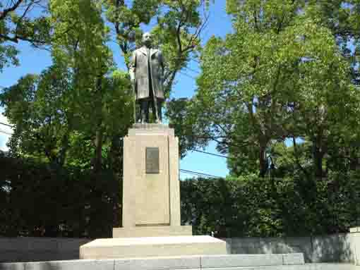 the statue of Gen Tanaka in green woods